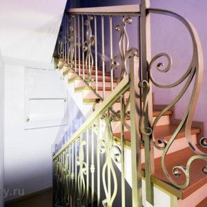 Кованые элементы лестницы и облицовка ступеней лестницы из бетона