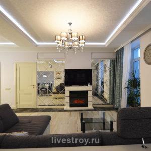 портальная зона с телевизором и облицовкой стен зеркальной плиткой. Освещение люстрой и встроенными в потолок светильниками